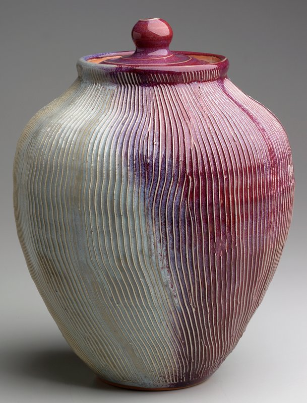 small foot flaring to a bulbous shoulder and inverting at mouth; lid with round knob; body of jar incised with vertical lines overall; incised swirl on cover; raspberry and pale blue glaze