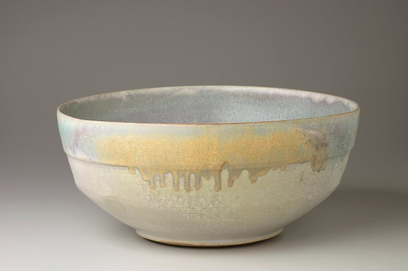 large, deep bowl with 6 small protrusions on interior; mottled blue, purple, pink, green, grey soft-toned glaze with subtile stripes on interior, bottom
