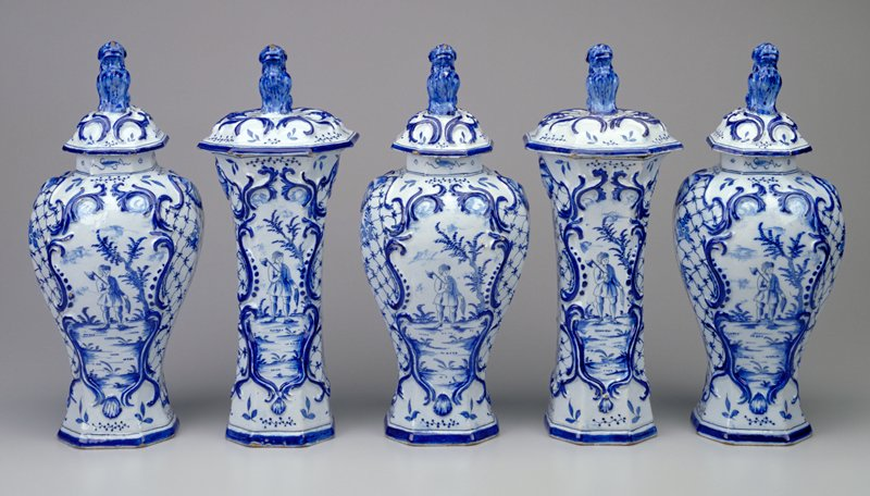 inverted pear-shaped vase with octagonal mouth; domed lid surmounted by dog; woodcutter next to a tree on front and back inside a Rococo cartouche; flowers and lattice throughout; blue and white