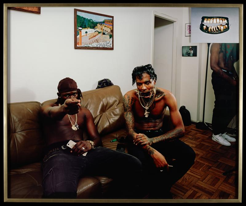 two shirtless black men seated on a brown sofa; man on left points outward toward the picture plane; man on right has an gold dental device holding his mouth wide open; another standing man at right with his face hidden by a photo collaged element on the outside of the frame with an image of a set of very old-fashioned dentures