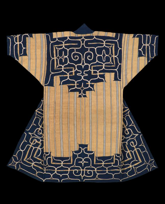 tan robe woven with vertical, navy blue and white stripes; navy blue applique trim on sleeve cuffs, bottom hem and body, collar, and back center; sleeve, back, and lower applique trim has curving, white and orange embroidery patterns; solid navy blue collar, with striped orange lining on interior neckline