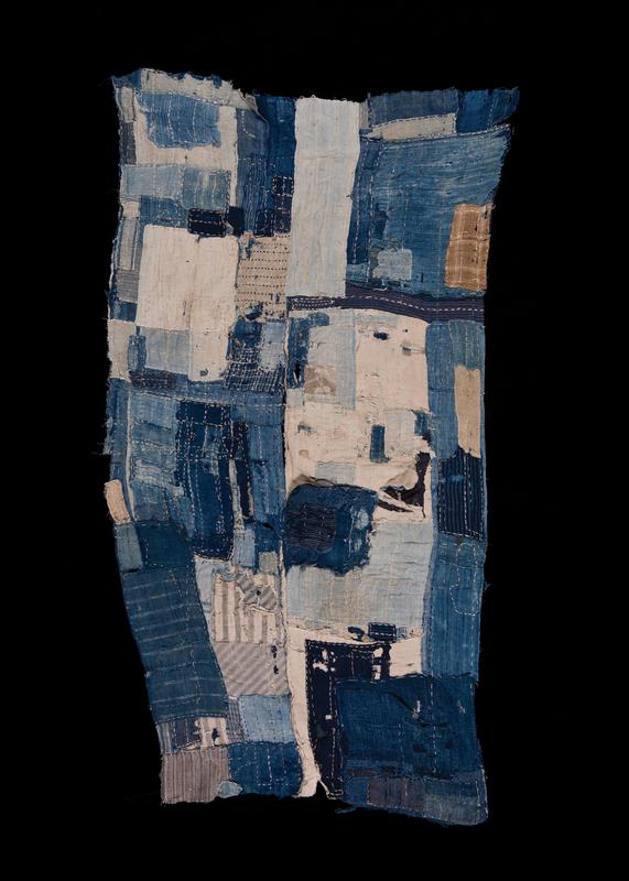 cloth patchwork panel in various shades of blue and white, some with patterns of stripes and plaids; blue and white checkered patch at corner