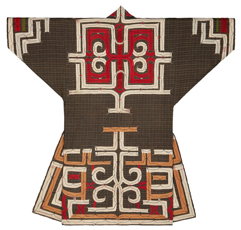 brown plaid background with stepped geometric pattern applique along lower half, in tan and white with red accents; large abstract squarish applique pattern on upper back in red and white, continuing over shoulders; stepped applique pattern in white with red and green accents on sleeves