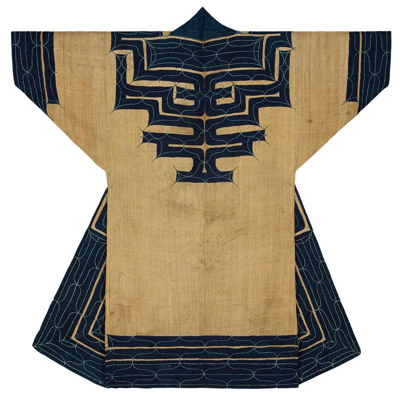 tan robe with navy blue applique trim on sleeve cuffs, bottom hem, yoke, and back center, all with lighter blue, curving embroidery patterns; points of embroidery pattern extend outside of navy applique patches; navy blue collar