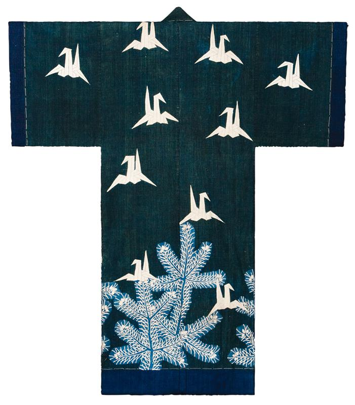 dark teal blue body with blue along sleeve edges and bottom edge; images of white origami cranes throughout front and back, with light blue and white plants along bottom