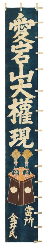 indigo-dyed cotton banner with inscription in Japanese characters in white; brown table or dais with two vases with fanned, pluming elements coming out of them; white cotton loop attachments