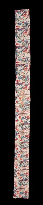long, skinny rectangular piece of fabric with blue, purple, green, red, and orange pattern on white background; green, blue, and purple grasses; red, orange, and pruple flowers; blue and purple butterflies; pattern changes direction at center