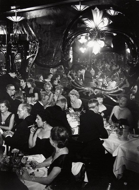 elegantly dressed people in crowded fancy restaurant, ornate mirrors along back wall.