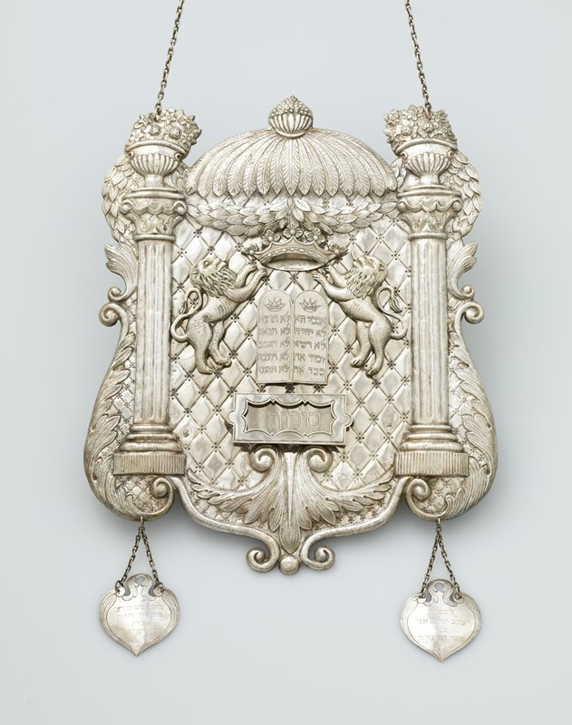 shield with 2 hanging pendants; pair of applied lions beneath an applied crown flank 2 tablets with applied box below; columns on either side