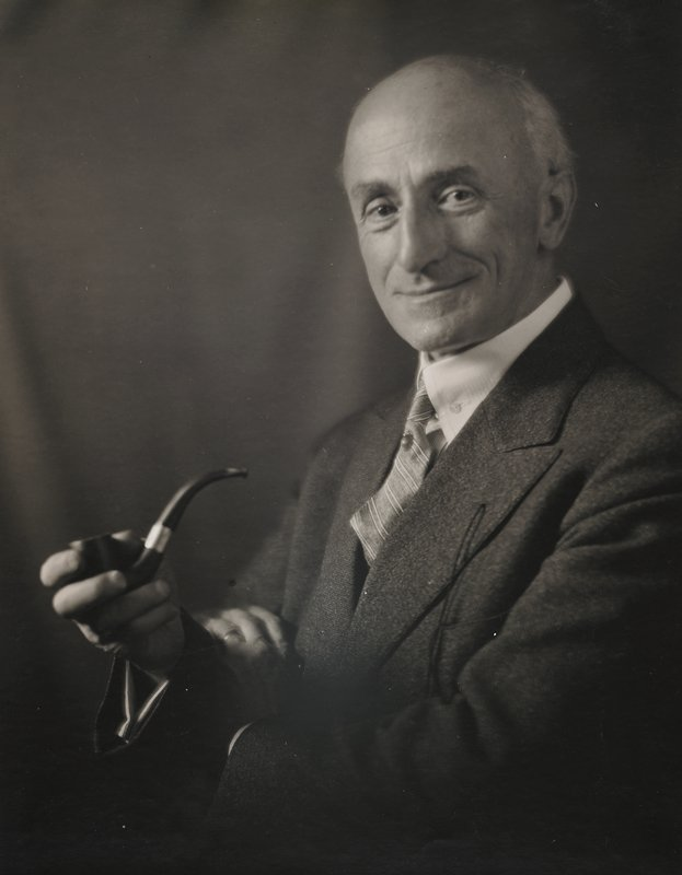 man facing forward, with body turned slightly toward PR; holding a pipe in his PR hand; PL hand on PR elbow; wearing dark suit and striped tie