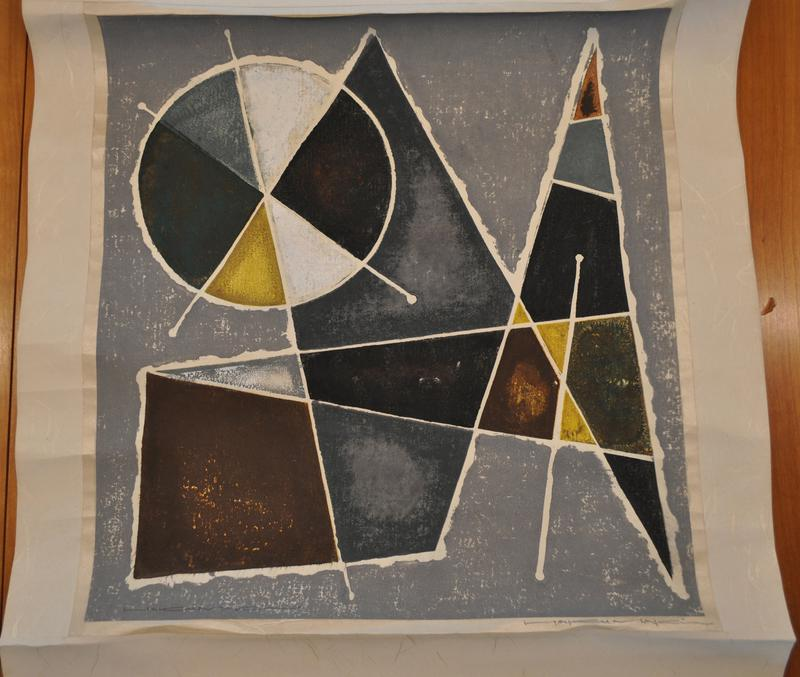 abstract image with grey and white mottled ground; white bordered geometric shapes in mottled jewel tones of gold, brown, green, and grey; circle in ULC broken into irregular segments, triangles, and various polygon shapes; print mounted as hanging scroll; wood roller ends