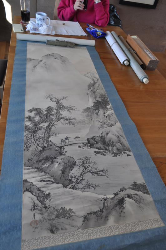 landscape with water and large mountain peak in background; bridge over water at middle ground center with two figures; greys and pale blue; blue brocade mount; ivory (?) roller