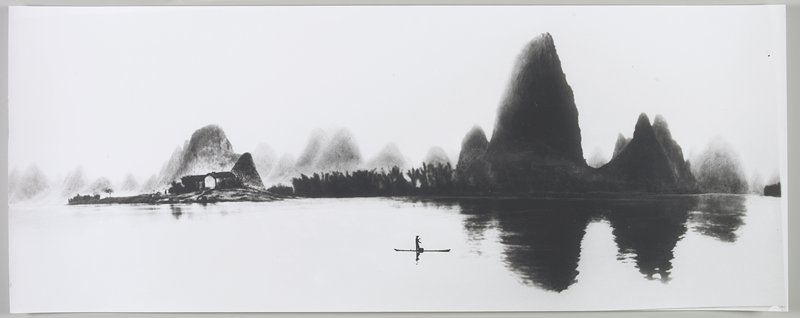 standing figure wearing a hat, rowing a boat near lower center; dark, curvaceous land masses at R, reflected in water; small building at L; Li River, Peoples Republic of China