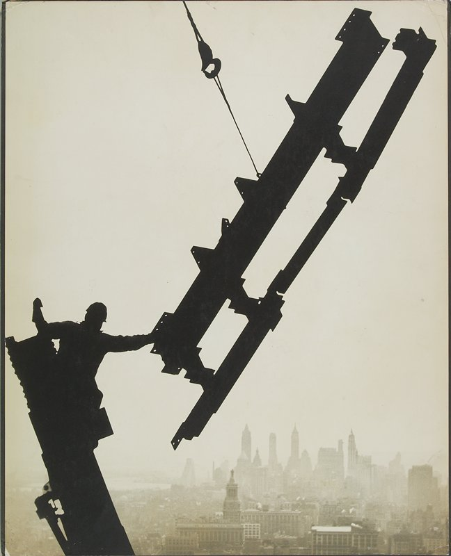 silhouetted figure wearing a hard hat, leaning on a beam and pulling a beam section on a hook toward him; city below
