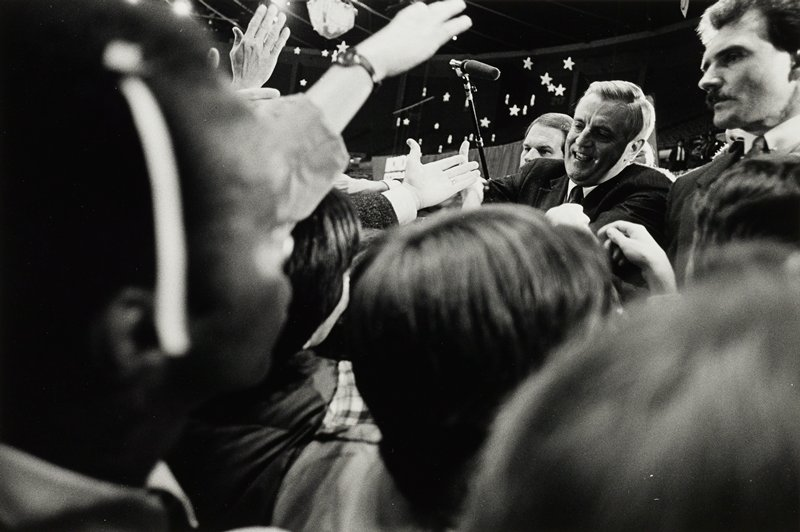 Walter Mondale shaking hands in a crowd at a political rally; body guards at each side, microphone extended over head and a sea of hands outstretched toward him