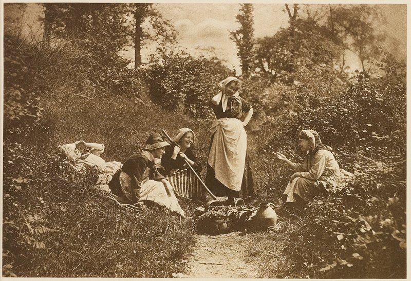 5 women (3 seated, one reclining, one standing) on a dirt path, with baskets and jugs before them; from a portfolio with essay on the photographer