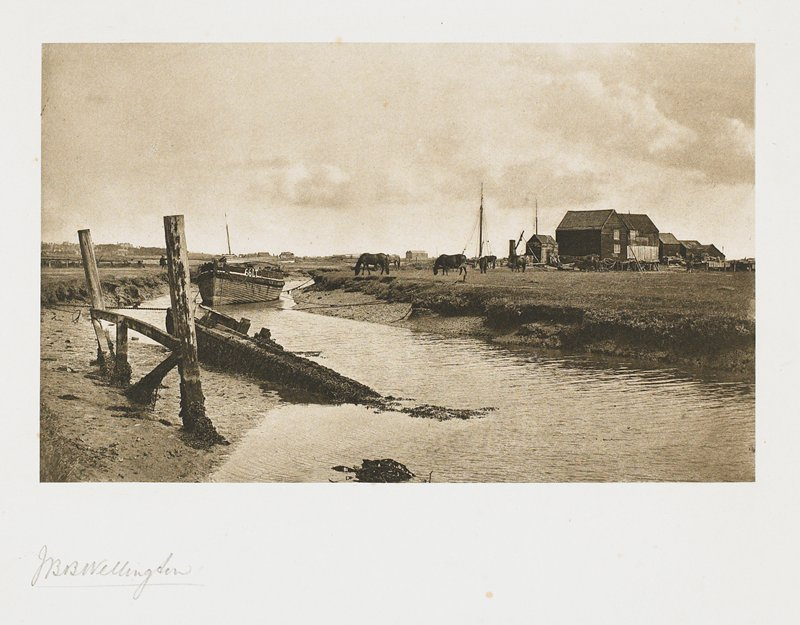 narrow stream with boat near center; buildings and horses at R; from a portfolio with essays on the photographer