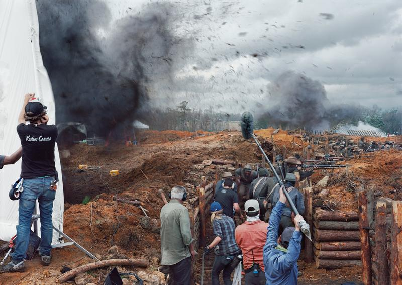 color image of battle scene on film set; black cloud of smoking rising on L, behind white screen and crew member facing away from viewer; reinforced trench dug into field at center and R, with more explosions in battlefield in background; production crew with equipment in trench foreground, with people dressed as soldiers further back in trench, firing muskets and facing battlefield