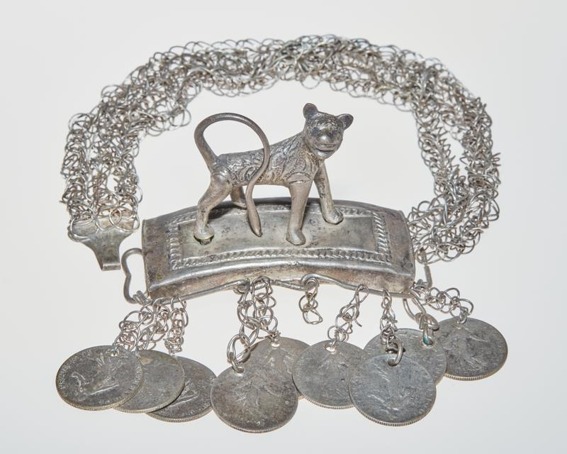 three looped chains attached to ring on base of curved platform with hook on other side; four legged animal with pointed ears stands on platform with tail curled over back, facing front right; patterning and details carved on animal and on top of platform; nine 50 centimes coins hanging from wires around platform on looped chains (one set of four, one set of three, one set of two with one empty chain link); all coins have a figure surrounded by text on one side and a branch of leaves with text on the other