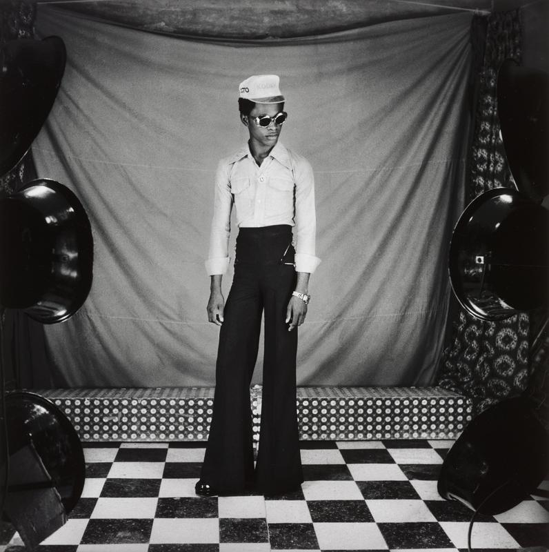 black and white image of young man wearing dark, high-waisted bell bottoms, light collared shirt, sunglasses, and hat, standing on checkboard floor; sheet hanging in background over floral-print platform; out of focus spotlights visible on left and right in foreground