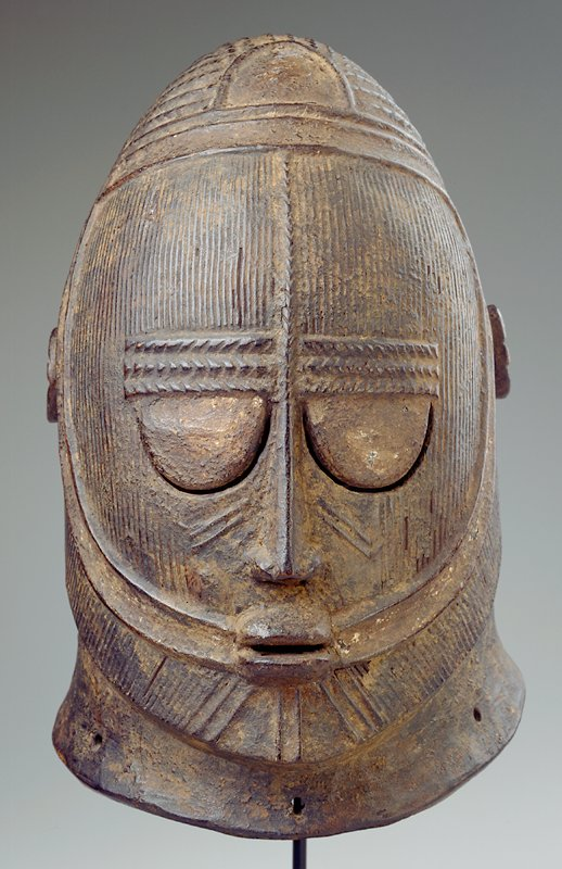 helmet mask with large eyes and pursed lips; spool-like ears; parallel vertical lines on face; 6 small holes on bottom edge