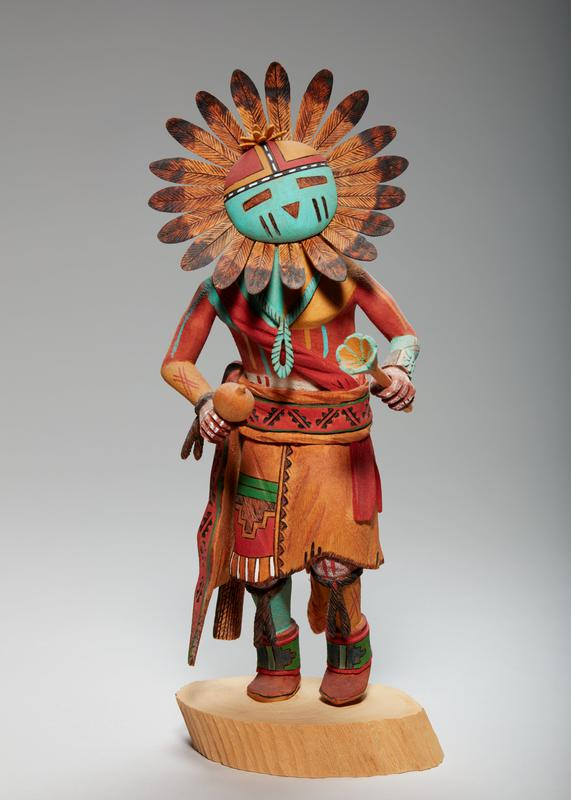 carved, painted figure, leaning slightly forward with PL foot raised slightly and an object in each hand (flat, round object on stick in PR hand; longer stick with flower in PL); teal, red, orange, and black round face with rectangular eyes and triangular nose, circle of black-tipped feathers lining edge of face; smaller bunch of feathers (or petals) on top of head; teal necklace, red sash over chest; orange skirt with colored pattern at front, red belt, and tail down backside; ties at knees over orange PL leg and teal PR leg; brown boots with red, blue and green pattern; figure standing on wood round