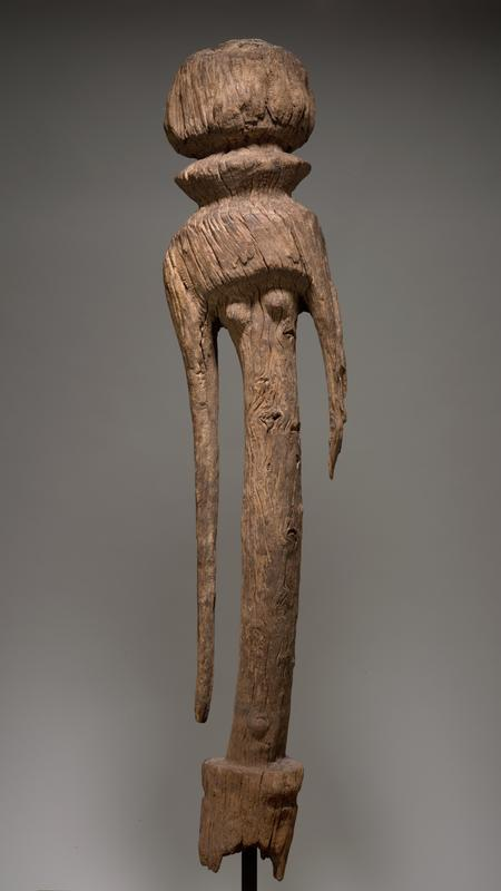 vertical carved figural sculpture with slight lean in posture; rounded head with collar-like ring around neck; PR arm longer than PL arm; knot in wood in torso where bellybutton would be; slight platform around bottom; affixed to black metal stand through bottom
