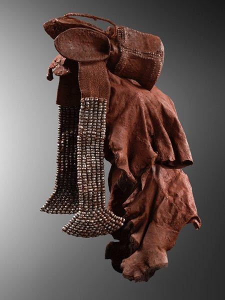 """headdress with crown-like top section with three """"ears"""" at top; silver beads around crown; two hanging wedge-shaped pendants covered overall with silver faceted metal beads; hide section with some fur attached to ends; encrusted overall with thick reddish pigment accretions"""