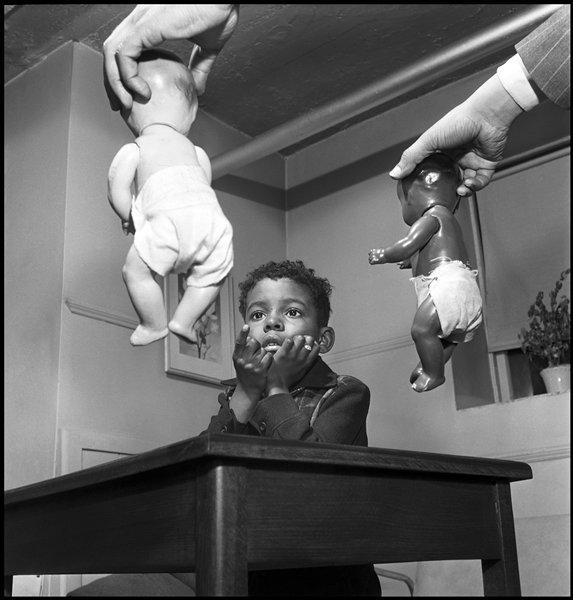 black and white image of a young Black child pointing at Black and white baby dolls being held by their heads in the hands on a white man; received in black frame