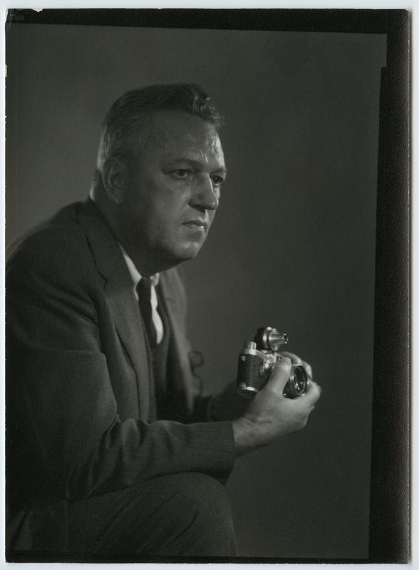 Black and white photograph of a seated man wearing a suit holding a camera and looking to the viewer's right; image cropped below his knee
