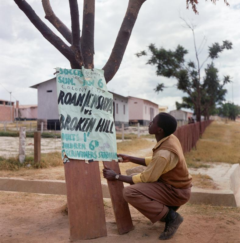 Color photograph of a man squatting down next to a sign with text on it