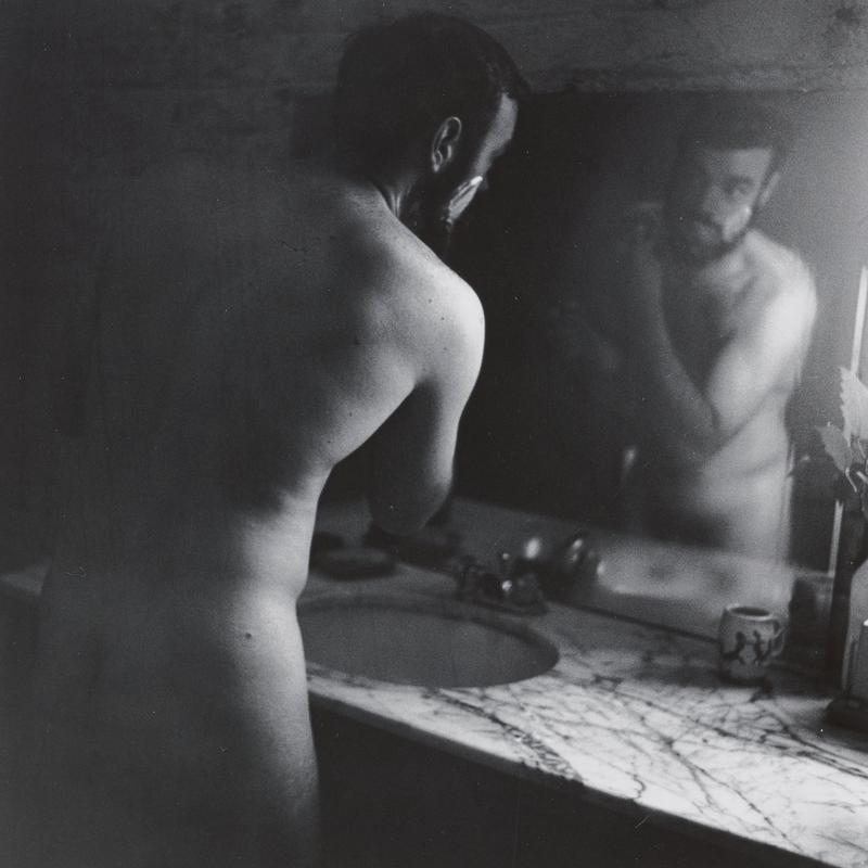 black and white image of a nude man at a bathroom vanity, shaving
