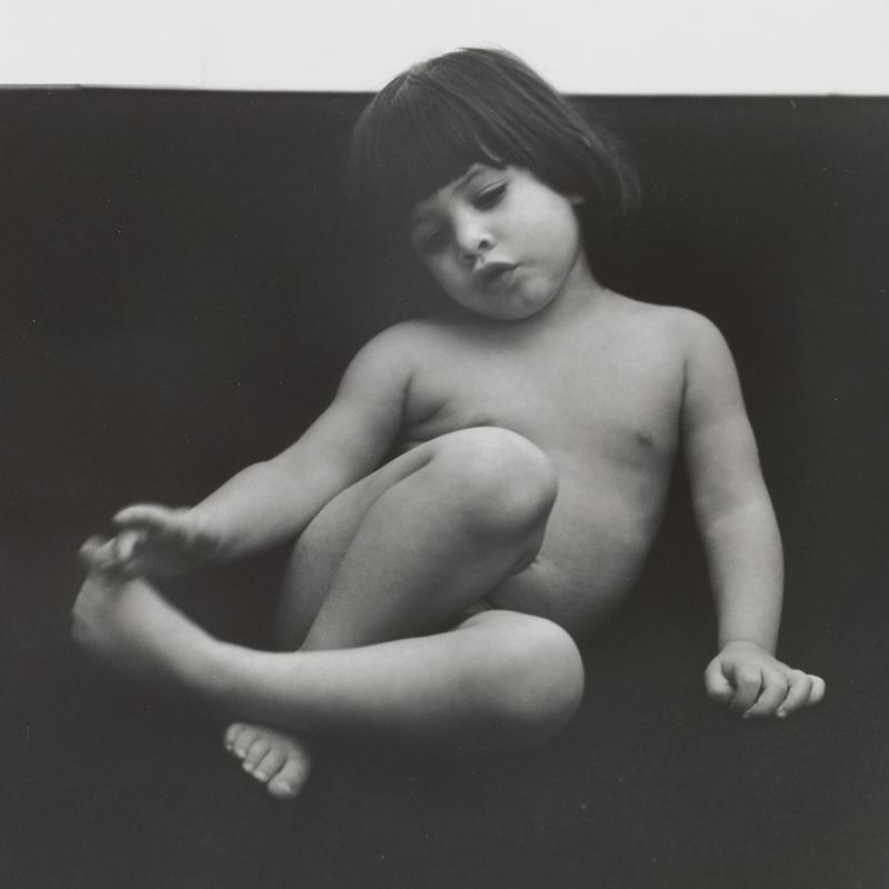 black and white image of a nude child with dark hair, with her knees drawn up and her PR hand near her PL foot