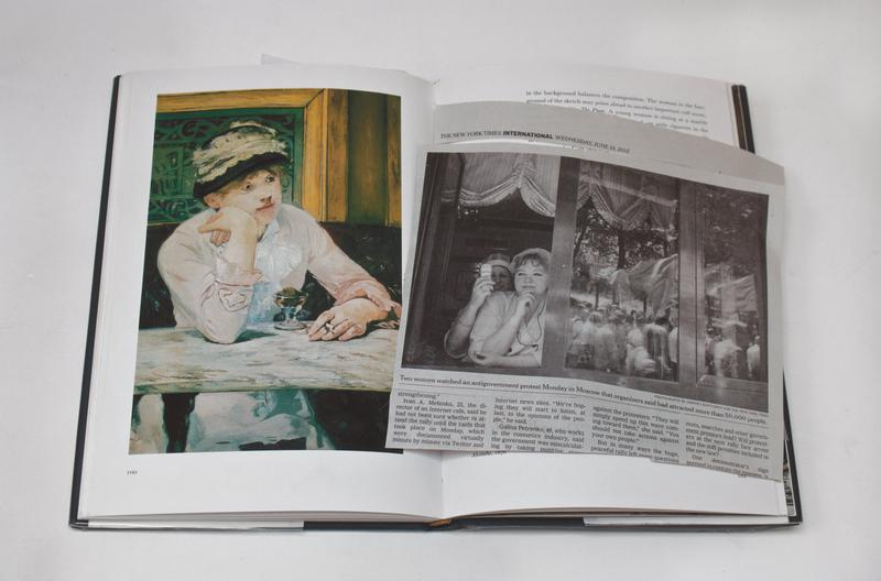 color image of a newspaper clipping with a photograph of two women looking out a window with marchers reflected in glass windowpanes on top of a book with a reproduction of a Monet painting of a woman wearing a pink dress, holding a cigarette, with a small glass in front of her