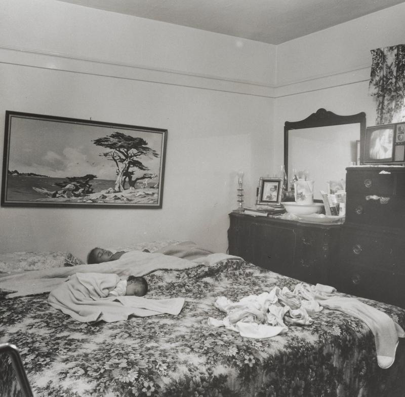 black and white image of a bedroom with baby and child sleeping on a bed with a floral bedspread; picture of a landscape with tree on wall above bed; small TV at right on chest of drawers