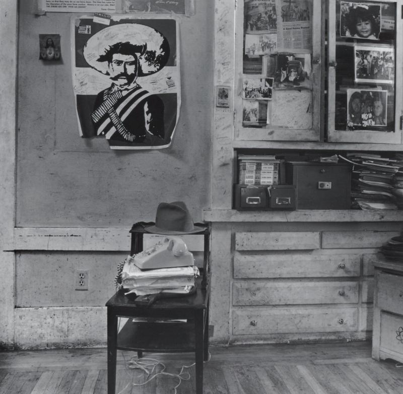 black and white image of a shabby room with a Pancho Villa poster on wall in ULQ; stand with a telephone and hat at center; built-in cabinet at right with file boxes, stacks of papers and photographs on glass doors; same image as .66