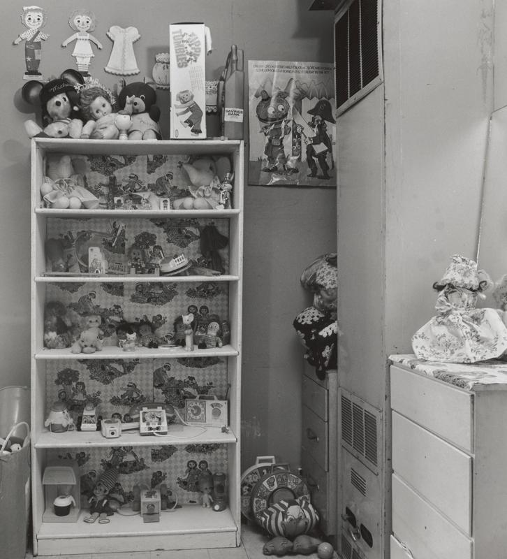 black and white image of a bookcase with Raggedy Ann motifs filled with various children's toys