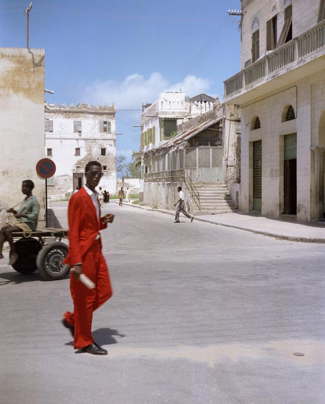 Color image of a man in a red suit crossing the street; white buildings and other figures in the background