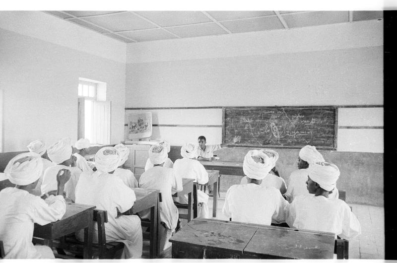 Black and white image of figures wearing white seated in a classroom