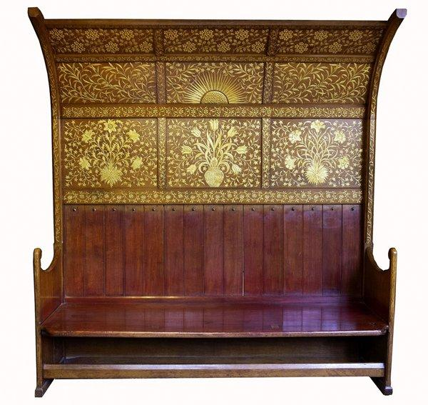 bench with tall back, curving forward at top; back and sides have applied gilded floral and sunburst designs; shipped with green cushion and curtain (reproductions)