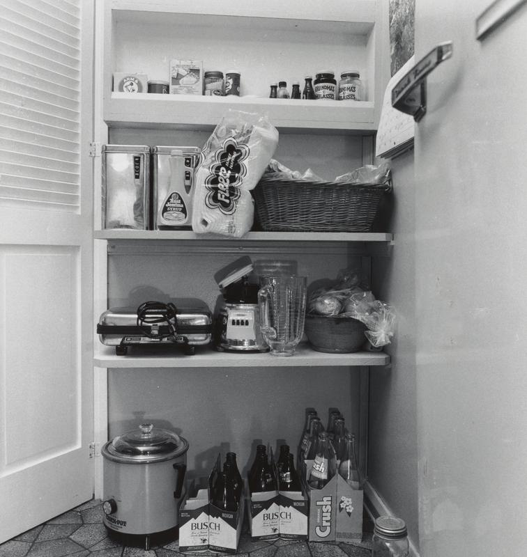 """black and white image of shelves in a kitched with Crock Pot, blender, waffle iron, basket, napkins, and empty bottles of Busch beer and Orange Crush in paper cartons; same room as in image titled, """"Pantry Shelf, Ruth's Home, Pomona Road, Ann Arbor, MI"""", but slightly different vantage point (.55); nearly idential to .65 (cropped slightly differently)"""