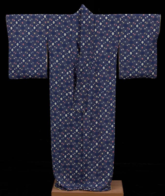 kimono with blue patterned fabric with white dotted lines forming diamonds and puckered various sized dots of pale blue, medium blue, red, yellow, and white