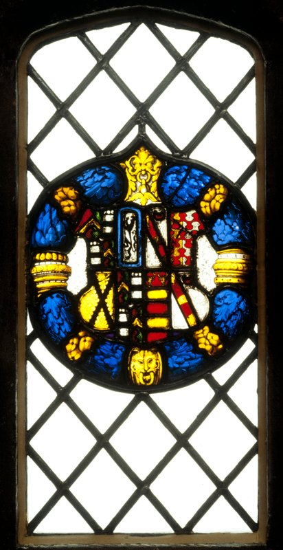 stained glass heraldic cartouche, containing the Arms of Sir Anthony Hungerford of Gloustershire impaled with those of his second wife, Dorothy Danvers; the shield is enciricled by a wreath of of blue and yellow foliage with yellow ornaments; Companion to 23.52.1 and contains the Hungerford, Burnell and Bottetort quarterings, impaled with Danvers (argent a bend gules charged with these martlets or, in chief a crescent of the second) in the first and fourth quarters Dauncey (per pale or and argent therr bars bebule gules) in the second and Barendes (gules two bars and in chief as many stags heads cabashed or) in the third
