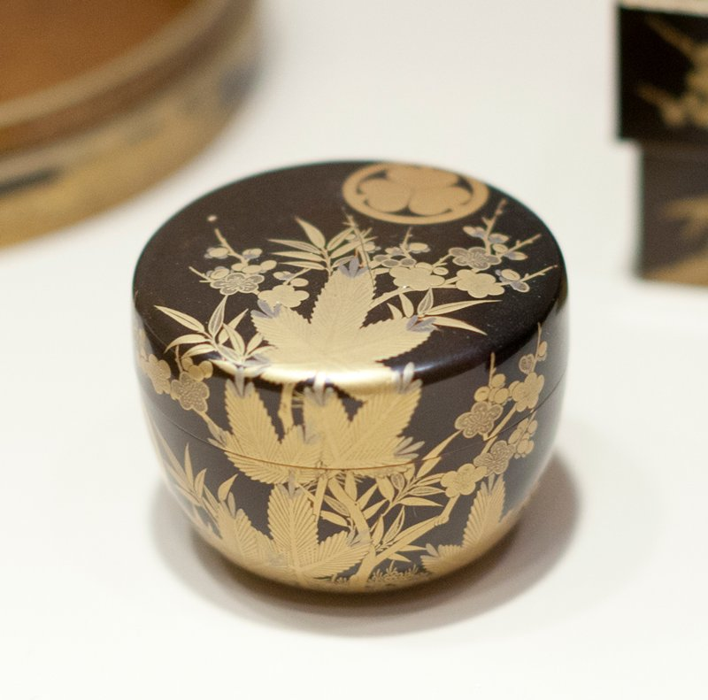 Bowl shaped toilet box of black lacquer with decoration in gold and copper of tree and floral motives; bearing three times the crest of the Tokugawa family, three asarum (ginger) leaves, their points together within a circle.