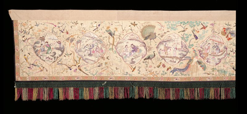 Large altar hanging; white satin ground on which medallions of figures in a floral background have been embroidered; green and red fringe along one side.
