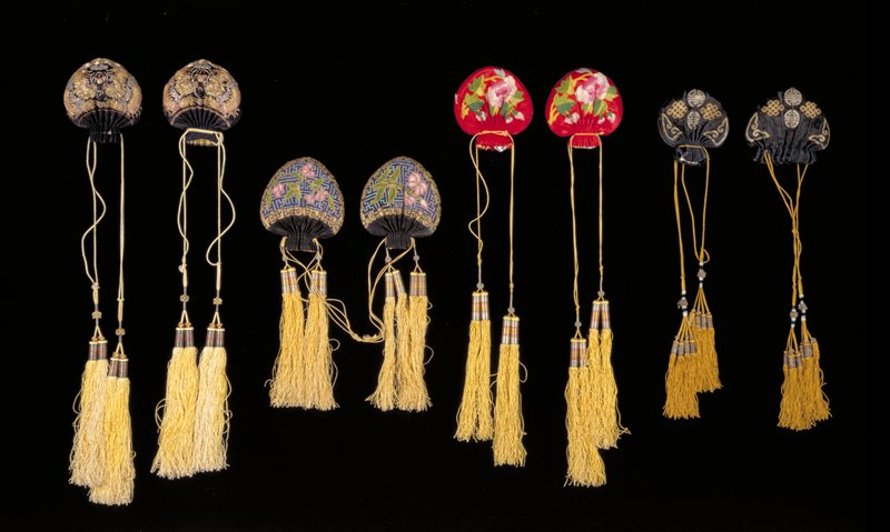 One of a set with 25.373.1. Two small bags of red satin with floral design in pink and green satin applique; yellow silk draw cords terminating in four large yellow tassels, wound with silver thread.