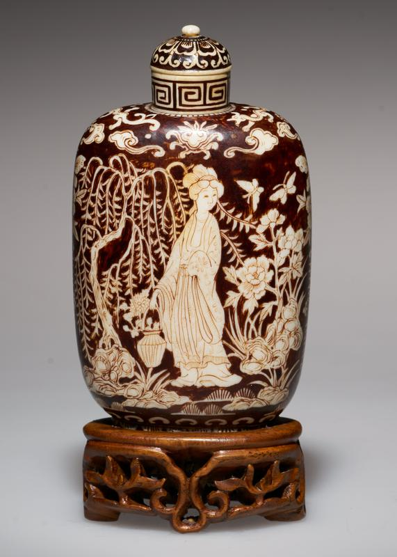 snuff bottle of ivory; ivory top; overlaid with black lacquer; design etched in lacquer; four graceful figures; jade flowers on table, beside which will be seen figure of a Princess; iris in background