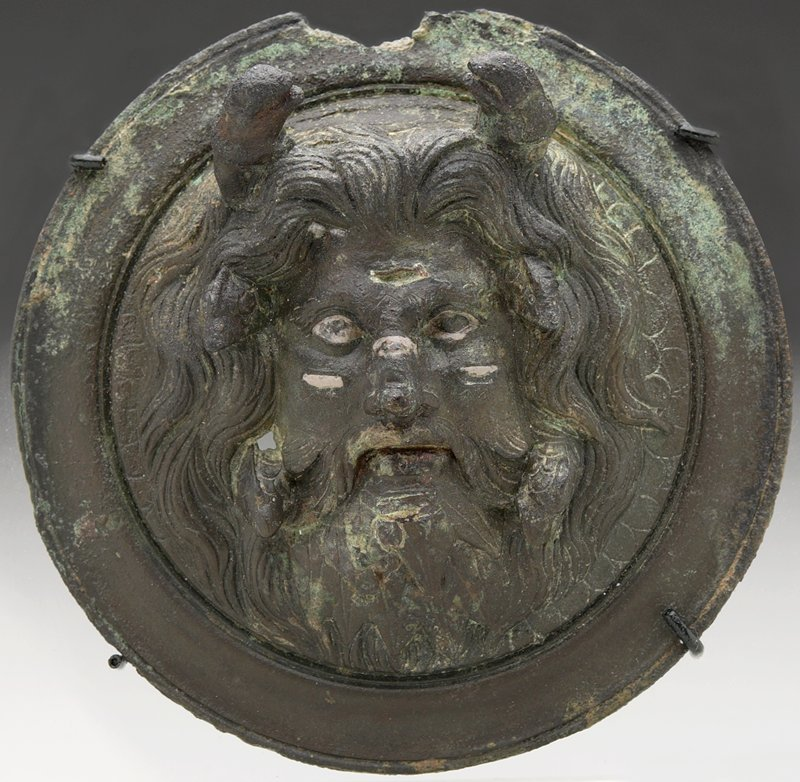Oceanus, god of the river. Frontal bearded head with silver inlaid eyes against a formalized background of the scales of his body, within a modelled rim. Small cheeks, nose and forehead. Two dolphins rampant above act as a crown; two fish peer from the locks of his hair; two more dive out of his beard. top of roundel broken and missing