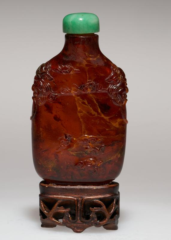Snuff bottle of tortoise shell with green jade top. Carved with bats.