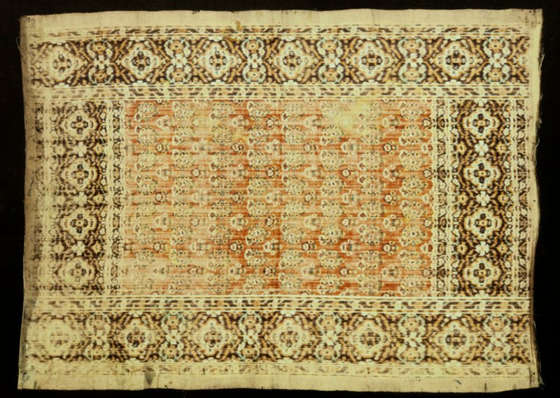 Panel, woven of velvet on cotton. Red ground, covered with alternating rows of small flowers and leaf-shaped motifs. Border composed of simulated Herati design in brown and black on white ground, alternating with double rosettes in same colors. Silk and cotton. N.B. These panel were sometimes used as prayer rugs.